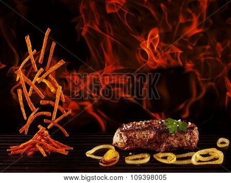 Grilled juicy beef steak with french fries - flames in the background, flying fried potatoes.