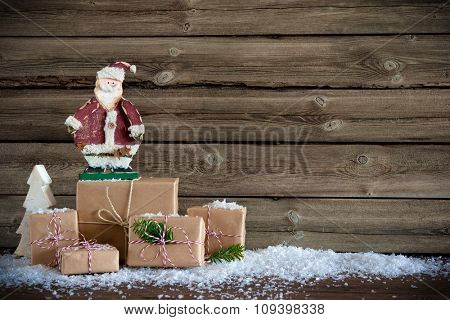 Christmas background with Santa Claus and gift boxes on wooden board