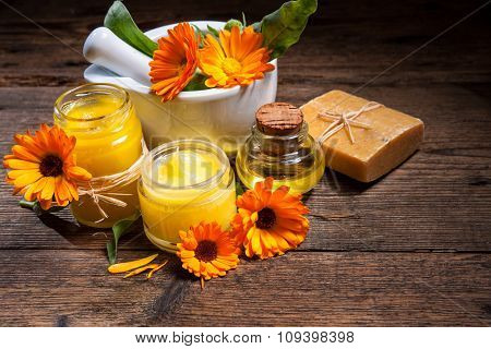 Homemade calendula ointment, soap and oil on wooden table