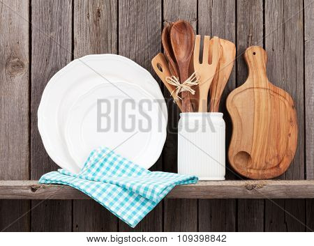 Kitchen cooking utensils on shelf against rustic wooden wall