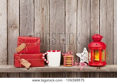 Christmas candle lantern, gift boxes and decor in front of wooden wall with copy space