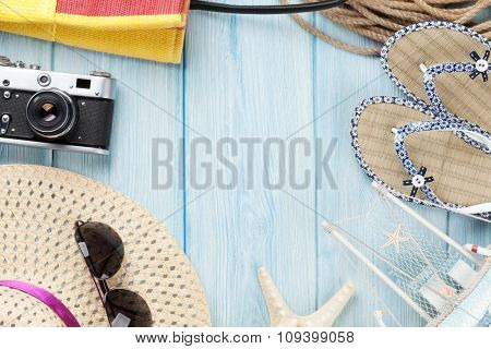 Travel and vacation items on wooden table. Top view with copy space