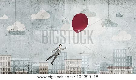 Young successful businessman in hat flies on colorful balloon