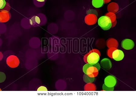 Abstract Blured Background Of Dark Multi Colored Shiny Christmas Tree Decorations At Night