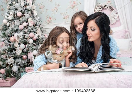 A young woman with children blue knit cardigan in the bed near Christmas wreath