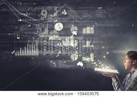 Young man with opened book in hands and infographs on wall blowing on pages