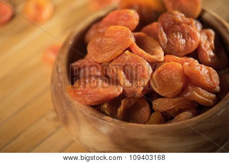 Dried apricots in a wooden bowl