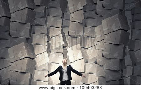 Businesswoman screaming among pile of carton boxes