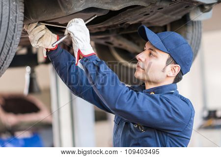 Portrait of a mechanic fixing a car in his garage