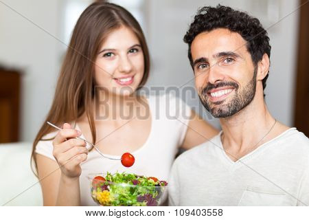 Couple eating a salad in the living room.