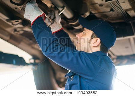 Portrait of a mechanic repairing a car in his garage