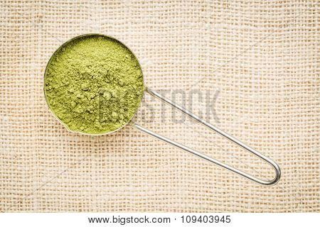moringa leaf powder in a metal measuring scoop against burlap canvas