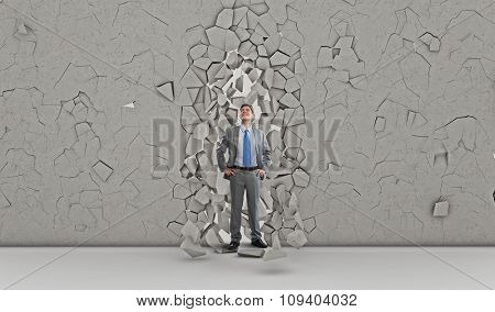 Young powerful businessman breaking through cement wall