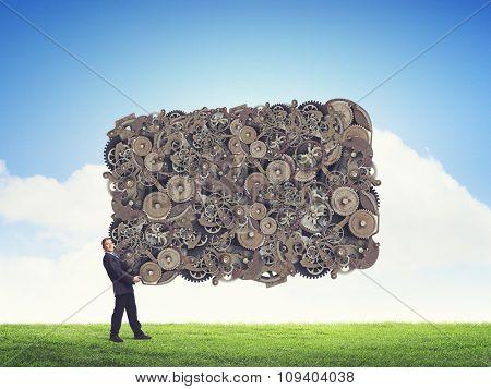 Businessman holding banner of gears mechanism as teamwork concept