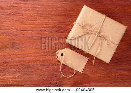 Gift Box Into Brown Paper Tied By Twine And Blank Tag On Old Wooden Table With Space For Text