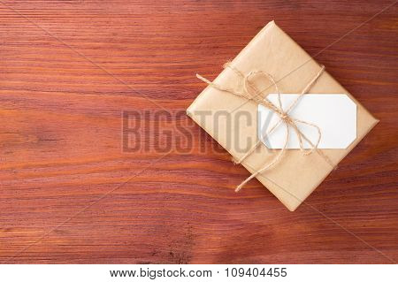 Gift Box Into Brown Paper Tied By Twine With Blank White Card On Old Wooden Table With Space For Tex