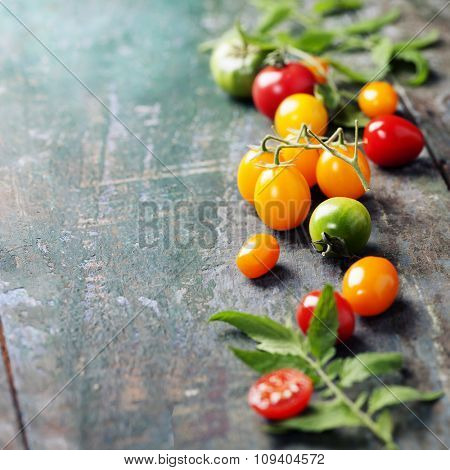 various of colorful tomatoes on wooden background. Cooking, Healthy Eating or Vegetarian concept.  Background layout with free text space.