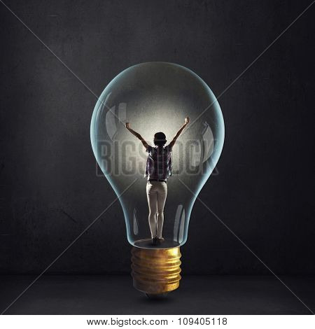 Cheerful girl inside of glass light bulb on dark background