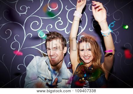 Happy young couple dancing in night club