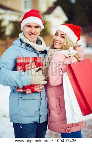 Cheerful young people doing Christmas shopping