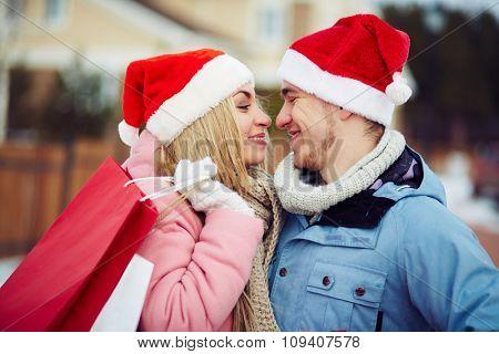 Couple in Santa hats kissing hats