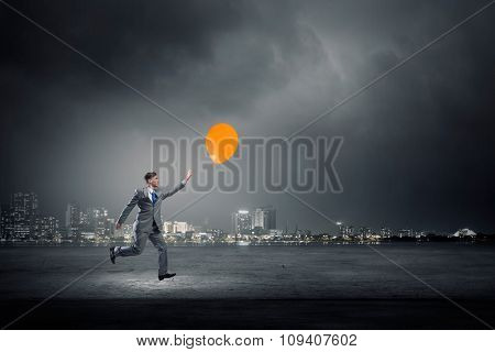 Emotional businessman running and trying to catch color balloon