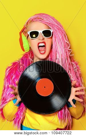 Glamorous modern DJ girl posing with vinyl record. Disco, party. Bright fashion.