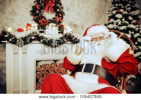 Good old Santa Claus sitting in a rocking chair in the room by the fireplace and Christmas tree, beautifully decorated for Christmas. Retro style.