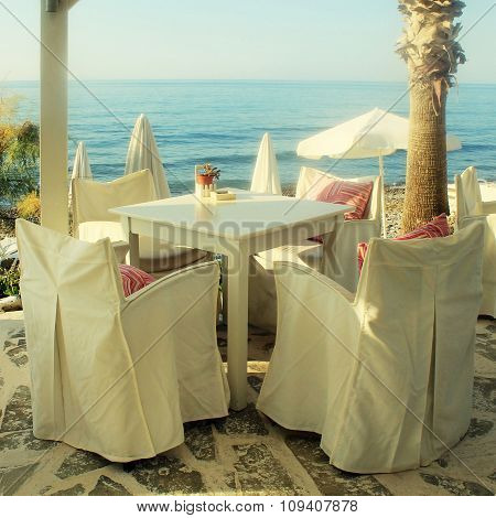 White Tables And Chairs In Greek Cafe By The Sea Coast, Crete, Greece