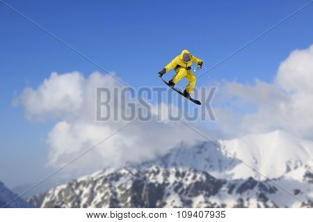 Cloudy mountain landscape with flying skier, extreme winter sport.