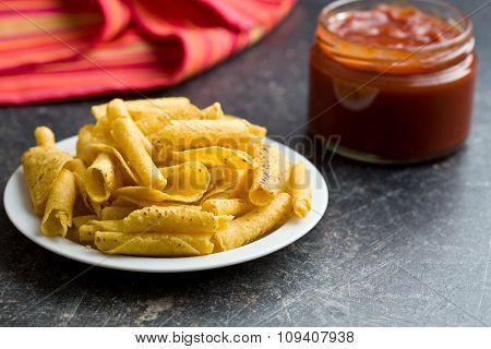 rolled nacho chips and salsa dip on kitchen table