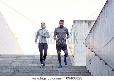 fitness, sport, exercising, people and lifestyle concept - couple walking downstairs on stadium