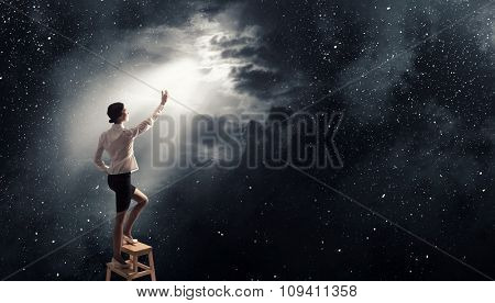 Businesswoman standing on chair and reaching light