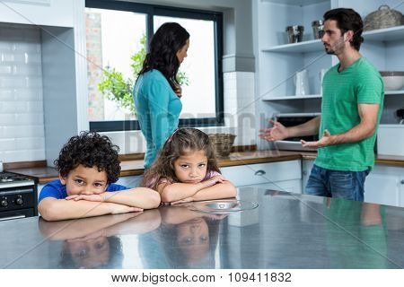 Sad children listening to parents argument in the kitchen