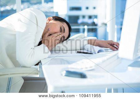 Yawning business woman near her pc at the desk in work