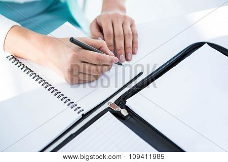 Businesswoman writing into notepad at the desk in work