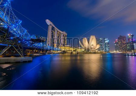 Singapore city skyline with Helix Bridge at the marina bay waterfront at night