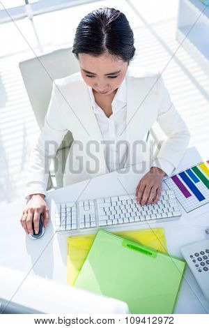 Businesswoman using her pc with documents at the desk in work