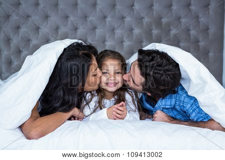 Happy parents kissing daughter under the blanket