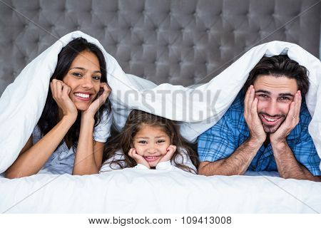 Happy family under the blanket posing for camera