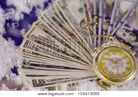 Christmas Pocket Watch Against The Background Of Dollar Bills Of Different Denomination.