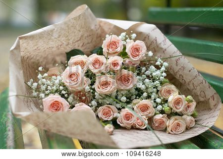 Beautiful bouquet in the paper on the bench