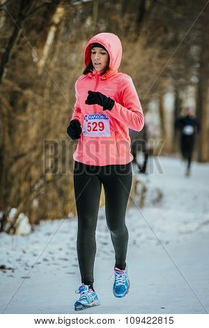 young girl runner runs at winter Park in snow