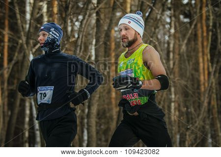 closeup two athletes middle-aged men running down track in winter forest