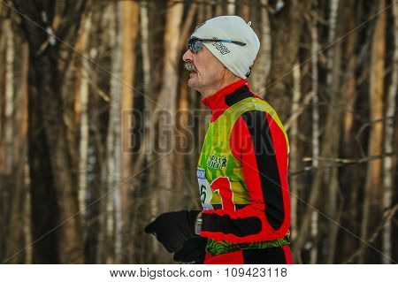 closeup of face old male runner in  winter forest