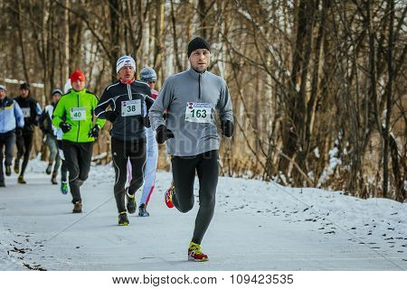 young man runs ahead of group athletes in winter Park