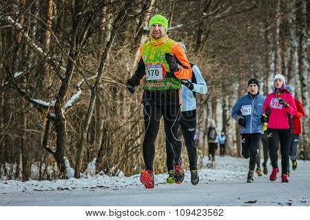 happy young athlete man running in front group of athletes in winter woods