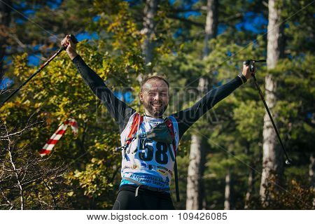 young male athlete is happy in hands of nordic walking poles