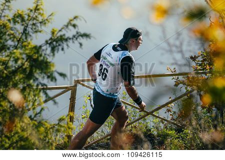 man athlete running on mountain trail. in background of mountain valley
