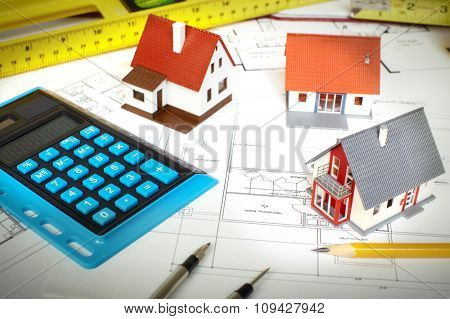 Little house and calculator on the table. Construction and architecture.
